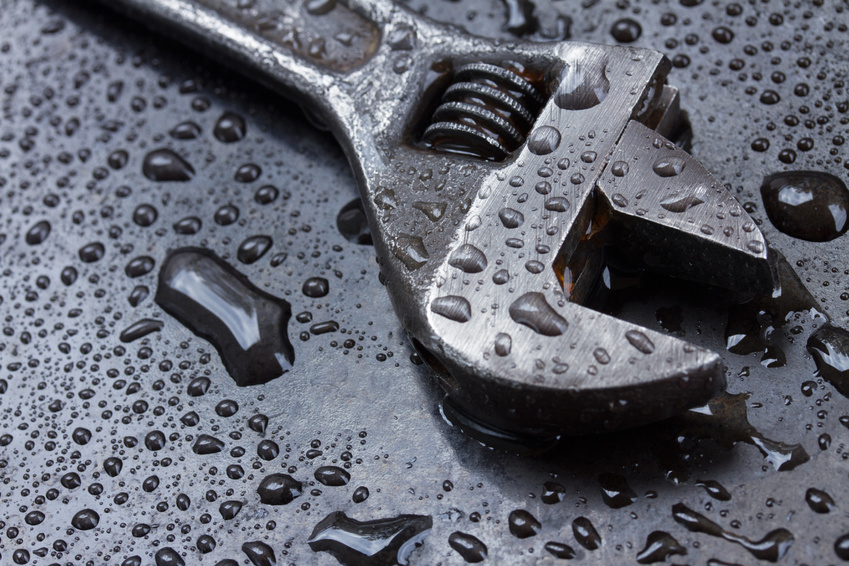 Adjustable spanner on black metal in water drops close up
